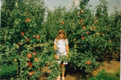 Neighbor Brianna in front of the apples