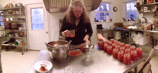 Marsha filling jars with marmalade.
